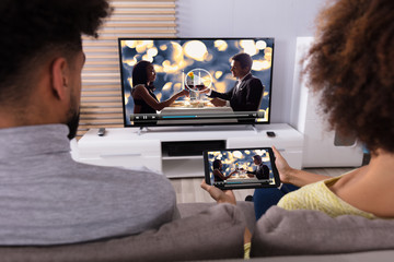 Couple Connecting Television Through WiFi On Digital Tablet