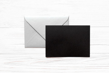 Silver envelope and black paper blank on white wooden background. Mockup for greeting card.