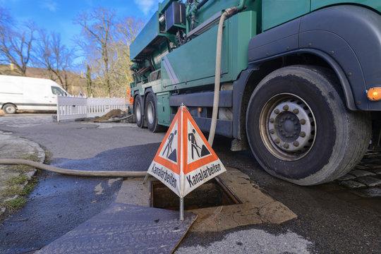 Warnschild für Kanalreinigung steht neben dem Spülwagen am Strassenrand