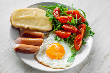 Breakfast which includes eggs, sausages, salad and toast with cheese
