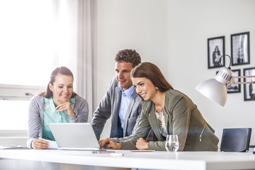 Happy young business people using laptop in office