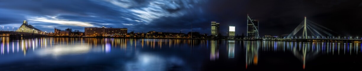Riga skyline with National Library, some skyscrapers and cable stayed suspension bridge. Night shot  with scenic water reflections in Daugava river waters