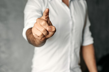 a man in a white shirt on a background of gray concrete pushes his index finger at the camera screen.