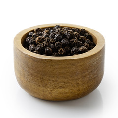 Whole black peppercorns in dark wood bowl isolated on white.