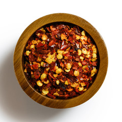 A pile of coarsely ground chilli peppers isolated on white from above.