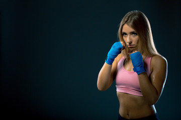 Portrait of a beautiful boxer girl with blue bandage on hands overdark background