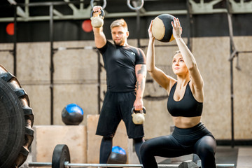 Young athletic couple in black sports wear training with weights and ball in the crossfit gym