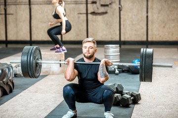 Handsome athletic man in black sports wear lifting up a heavy burbell with woman training on the background in the crossfit gym