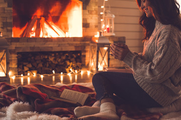 Young woman near fireplace at home winter concept holding cup