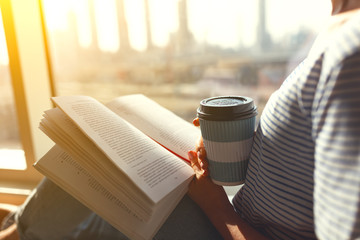 Women's hands with coffee and a book by   window