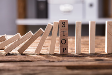 Falling Dominos Stopped By Wooden Blocks Showing Stop Text