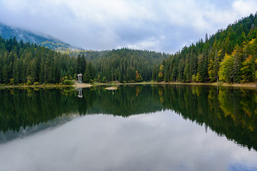 View of Synevir high-altitude lake by autumn day. The leaf fall forest is reflected in water of lake.