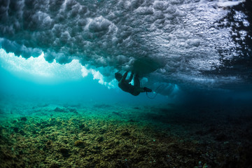 Lady surfer struggles between powerful ocean wave and sharp and shallow coral reef Wall mural