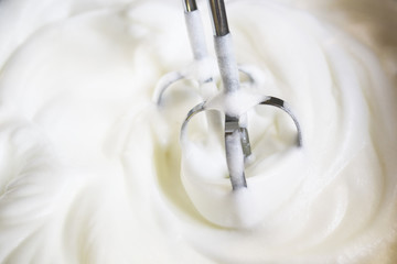 Mixer beaters partly emersed in whipped egg whites that have just been beaten until they are stiff
