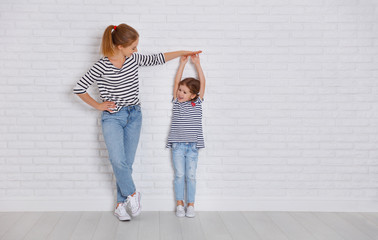 concept of the family. mother measures growth of child to daughter near empty wall