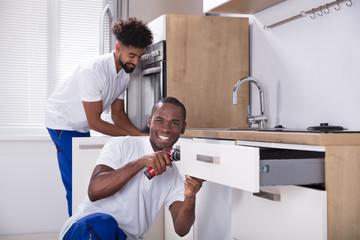 Repairmen Fixing The Wooden Cabinet In The Kitchen