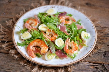 Healthy salad with shrimps, arugula, Parma ham, quail eggs and parmesan cheese.