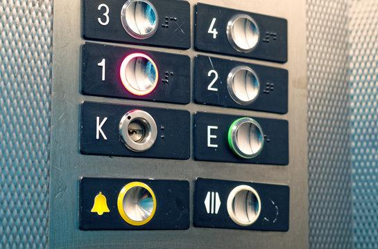 Aufzug Schaltknöpfe mit gelbem Hilfeknopf und Nummerierung vom Erdgeschoss bis zum 3. Stockwerk