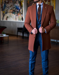 Male model in custom tailored trench coat and suit posing indoors