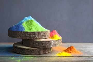 Bright colors for holi festival. Colorful holi paint on wooden saws on a wooden table. Close up with copy space