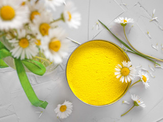 Bright colors for holi festival. Yellow holi paint in a bow (cup) with chamomile on a table top view. Close up with copy space. Natural organic pigment.