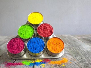 Bright colors for holi festival. Colorful holi paint in bows (cups) for spices on a grey wooden table. Close up with copy space. Natural organic pigment.