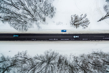 several cars drive along the road through the winter forest. Road seen from the air. Aerial view landscape. shooting from a drone