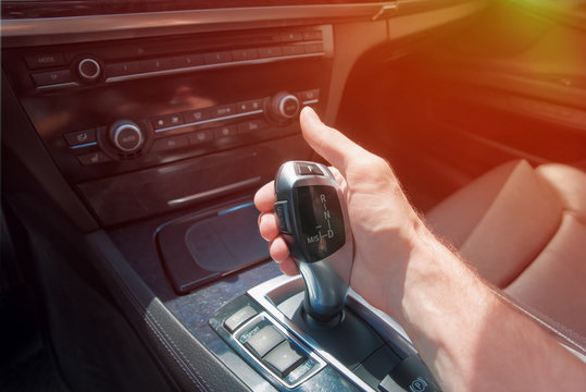 man's hand on an automatic gearbox. Automatic shift transmission. Sunlight.