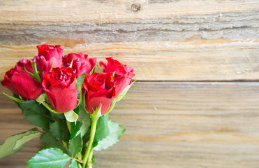 Bunch of red roses on wooden background.