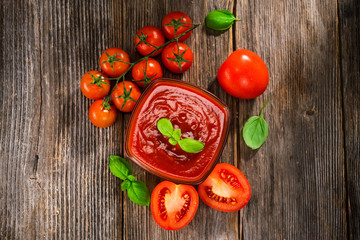 Tomato sauce and fresh tomatos on rustic background