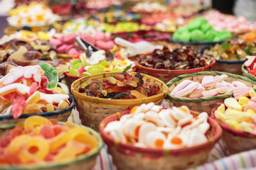 Close up of bowls filled with a large selection of different colourful soft candies including worms, gummy bears, gummy colas, gummy rings etc in a candy shop or a food market