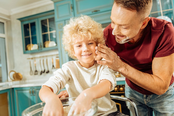 Positive emotions. Happy delighted cute boy putting hands into the bowl with flour and smiling while spending time with his father