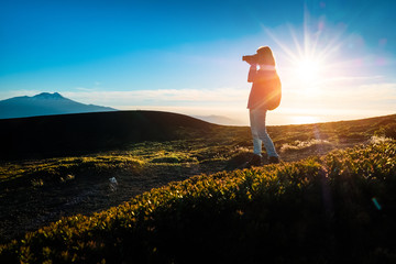 Hiker takes pictures from top of the mountain during sunset using the best of the golden hour