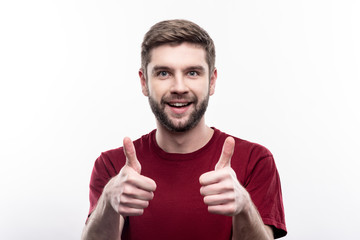 Good job. Cheerful young man in a burgundy t-shirt showing thumbs up with his both hands and smiling at the camera while posing isolated on a white background