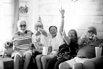 family of 4 seniors with white hair and a teenager celebrate in the mask laughing and playing sitting on the couch