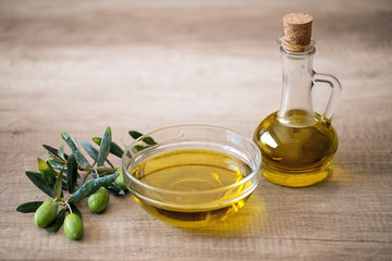 olive oil and olive on wooden background.