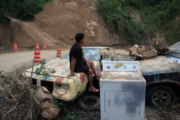 Ortiz sits on a car, that was already broken before Hurricane Maria hit the area in September 2017, in Utuado
