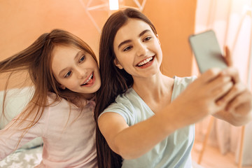 Precious moments together. Adorable teenage sisters sitting on the bed in their bedroom and taking selfies while one of the girls sticking out her tongue and touching hair