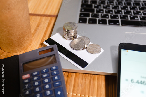 A stack of coins on credit cards next to the smartphone with