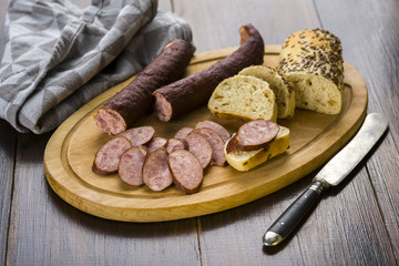 Sandwiches with homemade smoked sausage located on a board - food for consolation - tasty and healthy