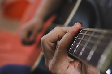 Musician hands playing chords on acoustic guitar