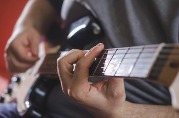 Musician hands playing chords on electric guitar