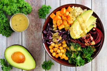 Buddha bowl with quinoa, avocado, chickpeas, vegetables on a wood background, Healthy eating concept. Overhead scene.