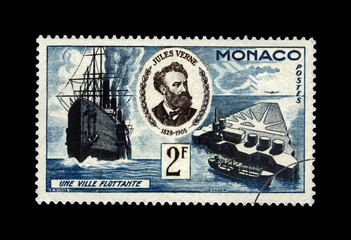 Jules Verne (1828-1905), famous science writer and Floating City, Monaco, circa 1955. canceled vintage postal stamp isolated on black background.