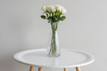 Close up of white roses in glass vase on round table against beige wall