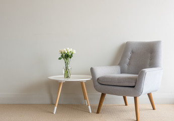 Retro armchair and small round table with white roses in glass vase against beige wall