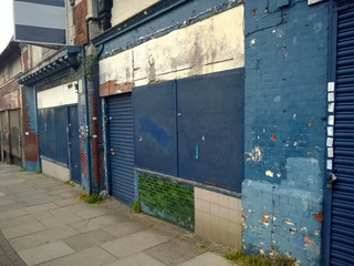 a row of abandoned stores with boarded up shop fronts with crumbling facades and peeling blue paint in an urban street