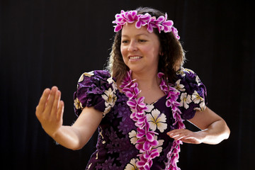 Smiling female Hawaiian girl dancing and singing with musical instruments like the ukulele