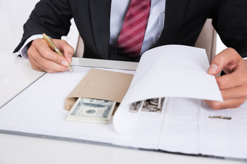 Businessman giving money in the envelope while making signed the document file.