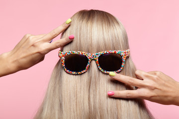 Rear view of young woman. Blond stright hair with fun sunglasses